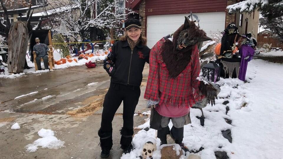 Une femme se tient à côté d'un loup-garou, une des décorations d'Halloween parmi tant d'autres.