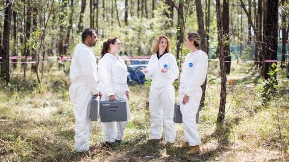 Quatre personnes en combinaison blanche discutent dans un boisé.