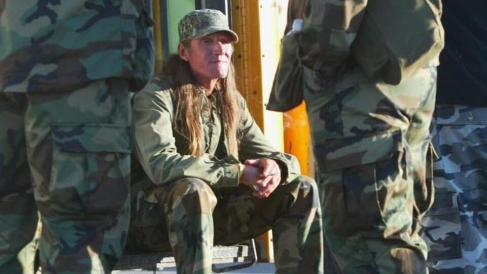 Un mohawk en habit militaire est assis près d'une demeure.