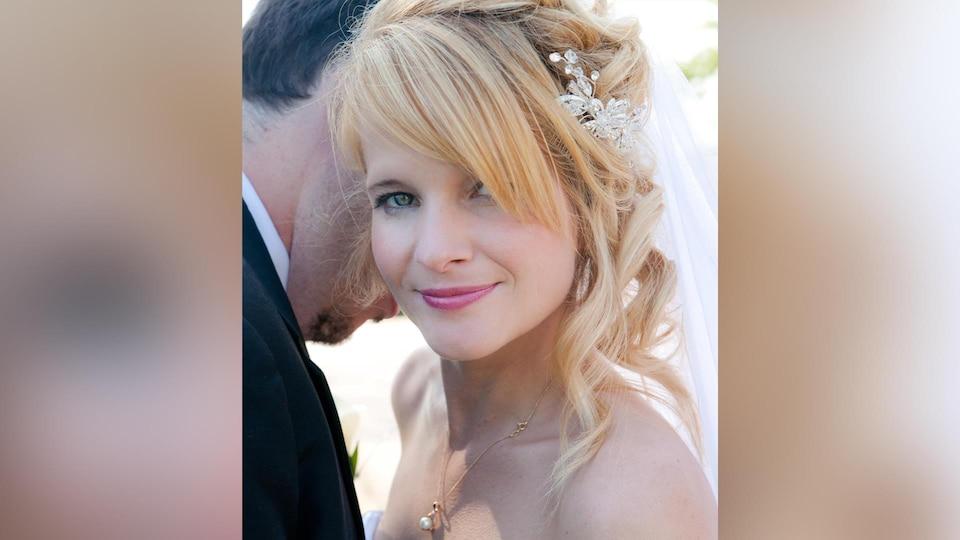 Portrait de la dame, habillée en robe de mariée. Elle est blonde et sourit à la caméra.