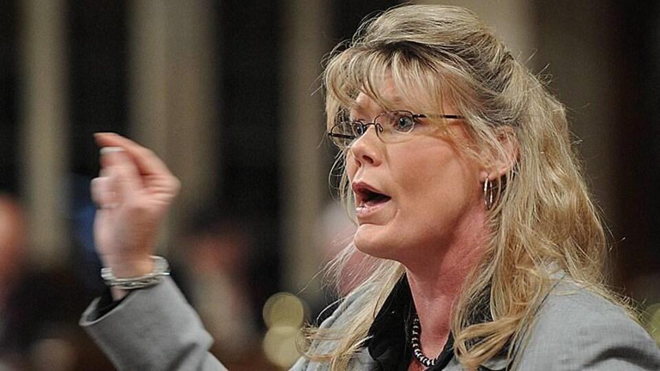 Une femme blonde à lunettes parle en gesticulant.