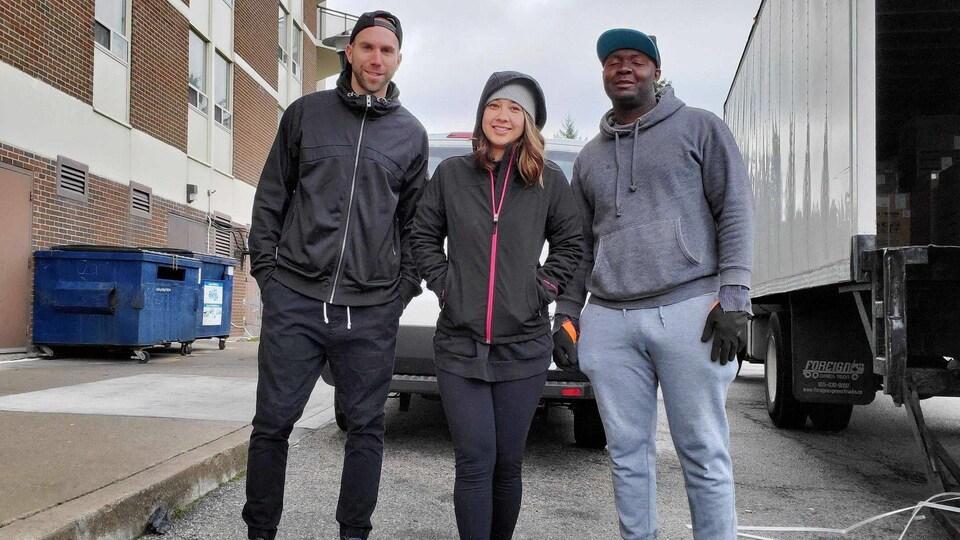 Trois personnes avec des gants de déménageur.