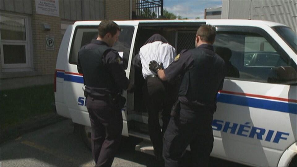 Deux shérifs escortent un détenu