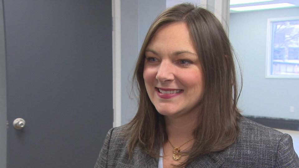 Une femme, souriante, dans un bureau.