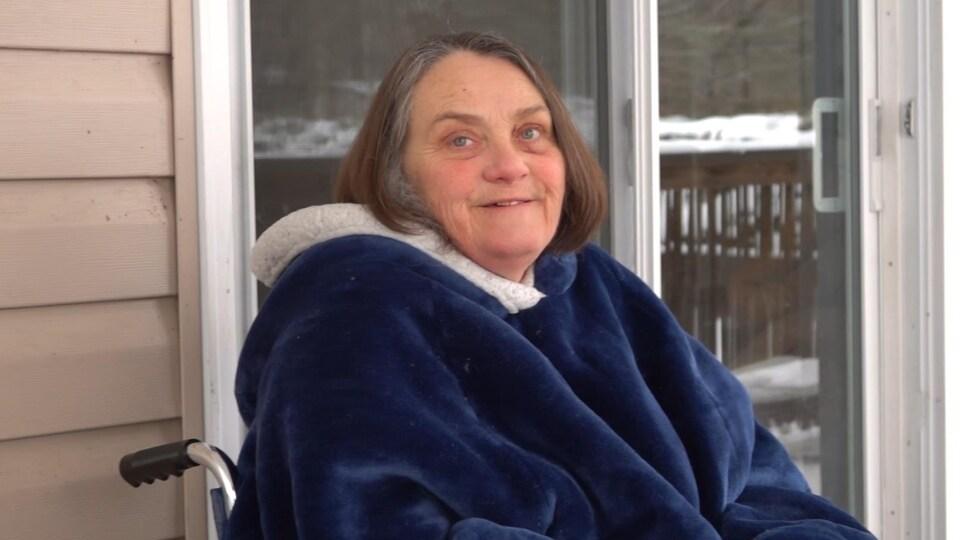 Sherry Anderson Mcfarlane est assise dans son fauteuil roulant sur le porche de sa terrasse.