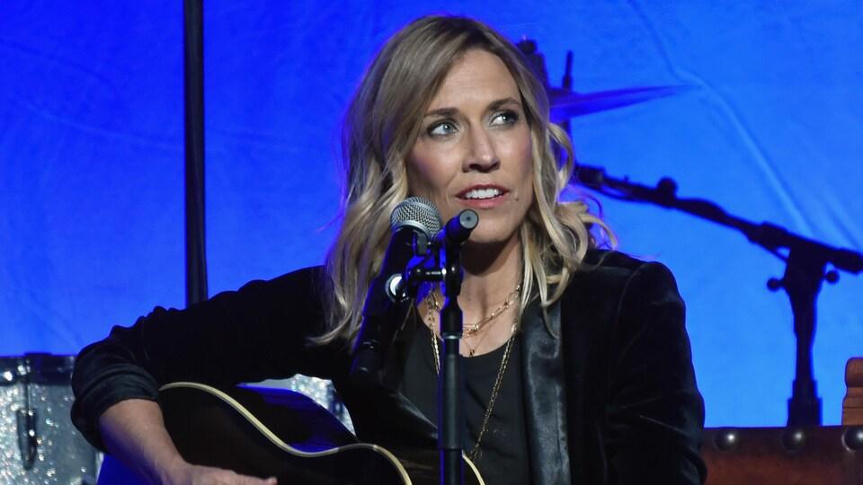 La chanteuse joue de la guitare.