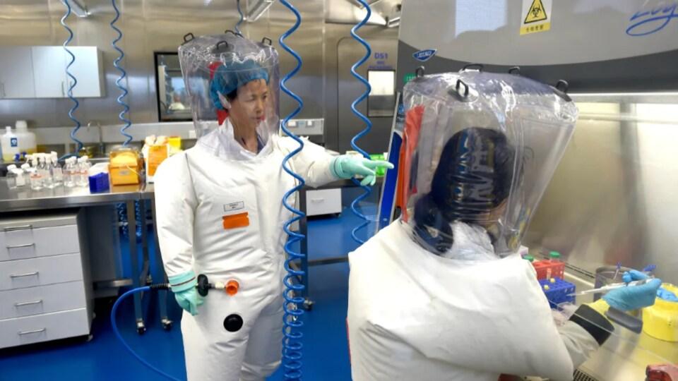 On voit des laborantins vêtus de combinaisons dans un laboratoire qui étudie les pathogènes. Debout, Mme Shi, concentrée sur son travail.