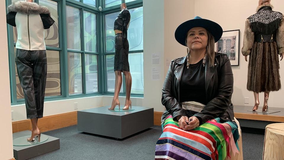 L'artiste et designer Sho Sho Esquiro assise avec en arrière-plan des mannequins vêtus de robes.