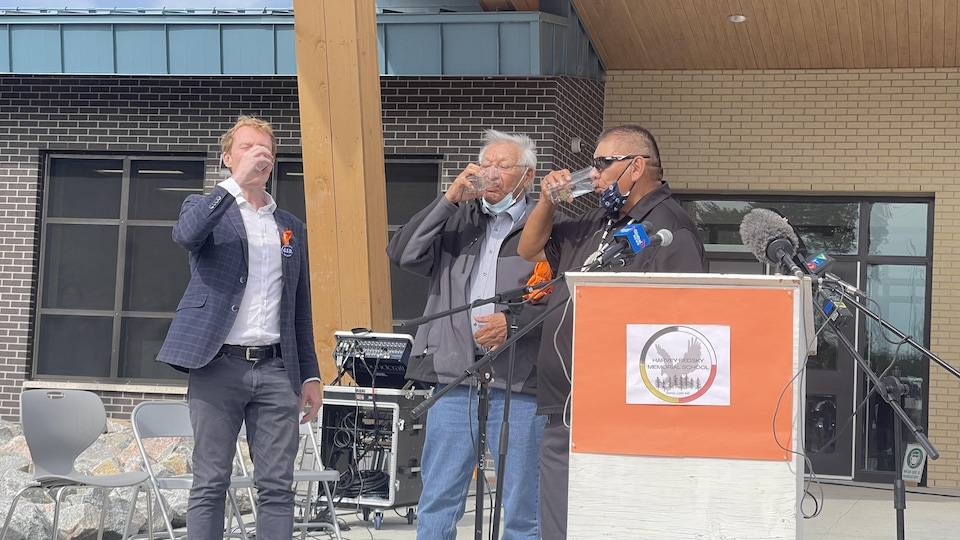 Trois hommes devant un lutrin boivent de l'eau.