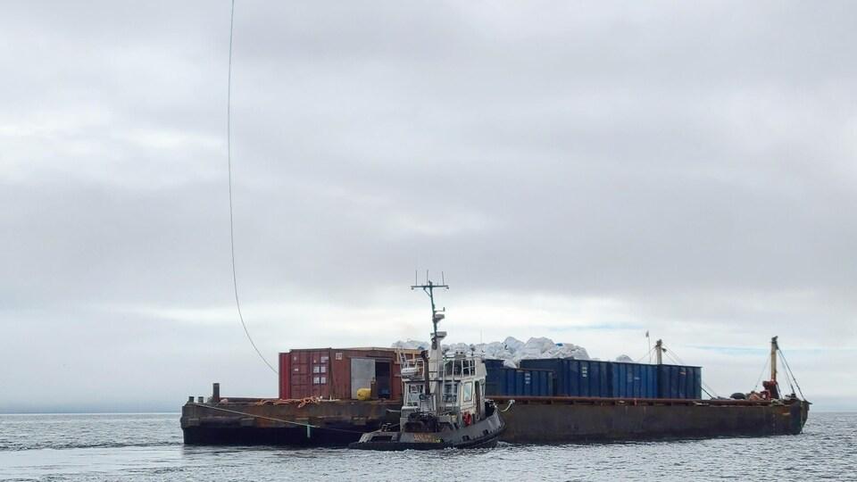 Un hélicoptère survole une barge et un bateau.