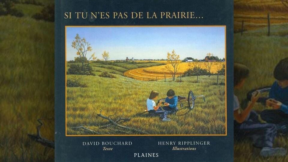 Deux enfants sont assis dans de l'herbe avec un vélo couché par terre.