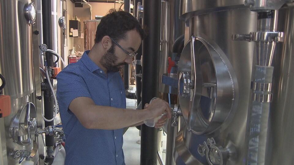 Jonathan Gaudreault, copropriétaire et maître brasseur, en train d'utiliser des cuves de bière en métal.