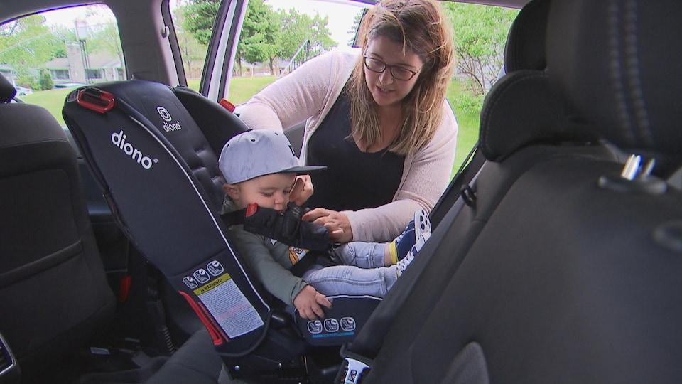 Marie-Christine Gervais attache son fils dans son siège d'auto.