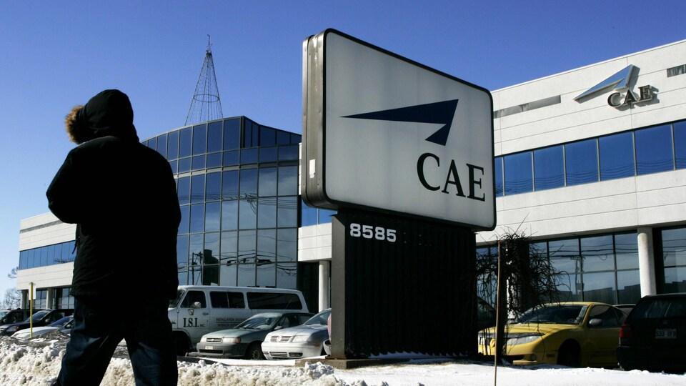 Un piéton passe devant le siège social de CAE à Montréal.