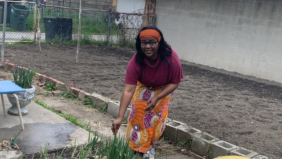 Une femme est dans son jardin. Elle tient une plante.