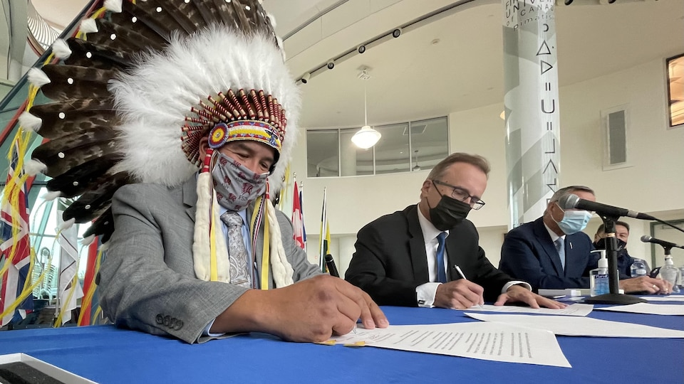 Le chef de la FSIN, Bobby Cameron, et le ministre saskatchewanais Jim Reiter signent une entente au sujet des casinos en ligne.