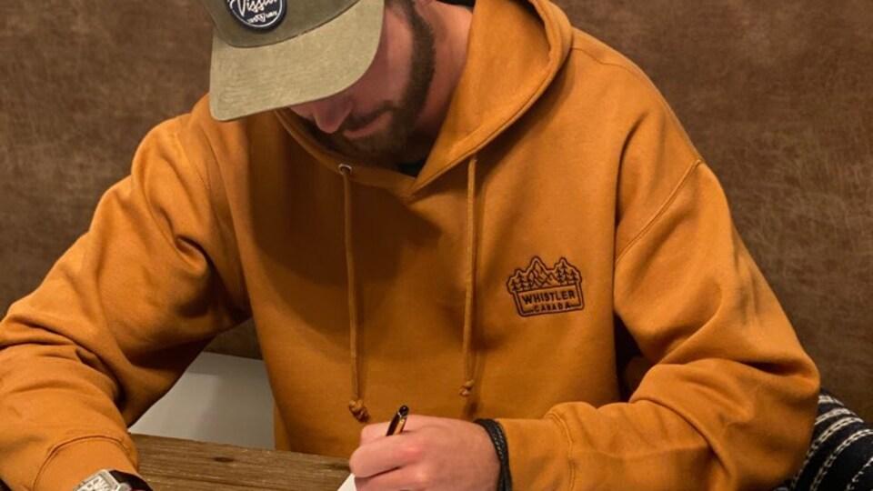 Joel Edmundson est assis à une table, il est vêtu d'un chandail à capuchon et d'une casquette. Il signe son contrat.