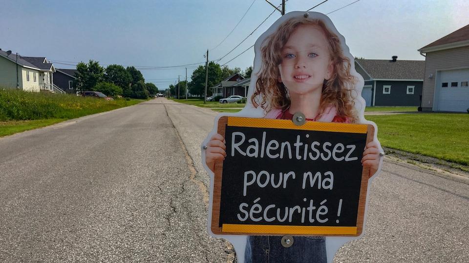 Panneau d'un enfant qui tient un tableau qui dit « Ralentissez pour ma sécurité », au centre d'une rue résidentielle à Saint-Narcisse.