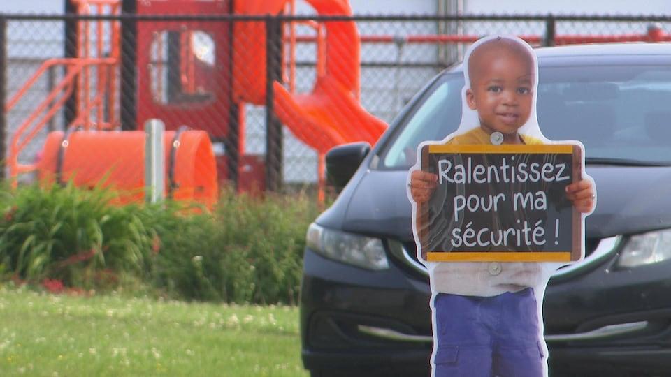 Silhouette où on peut lire : «ralentissez pour ma sécurité!» à Saint-Narcisse, devant un  jeu d'enfant et une voiture.