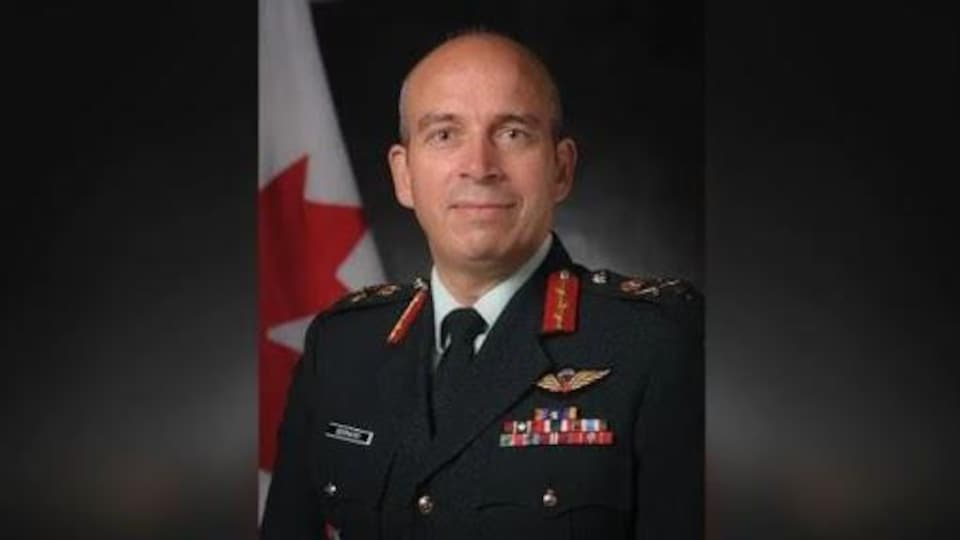 Un militaire en uniforme devant un drapeau du Canada.