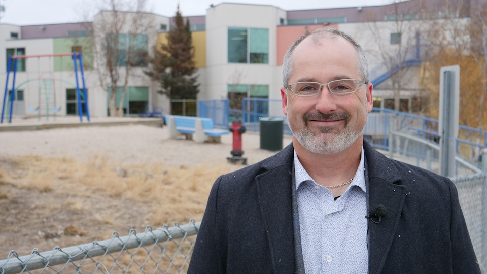 Simon Cloutier se tient devant l'École Allain-St-Cyr, à Yellowknife.