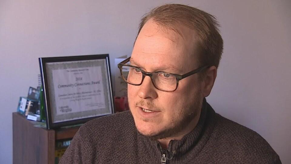 Gros plan sur le visage de Simon Enoch qui répond aux questions d'un journaliste.