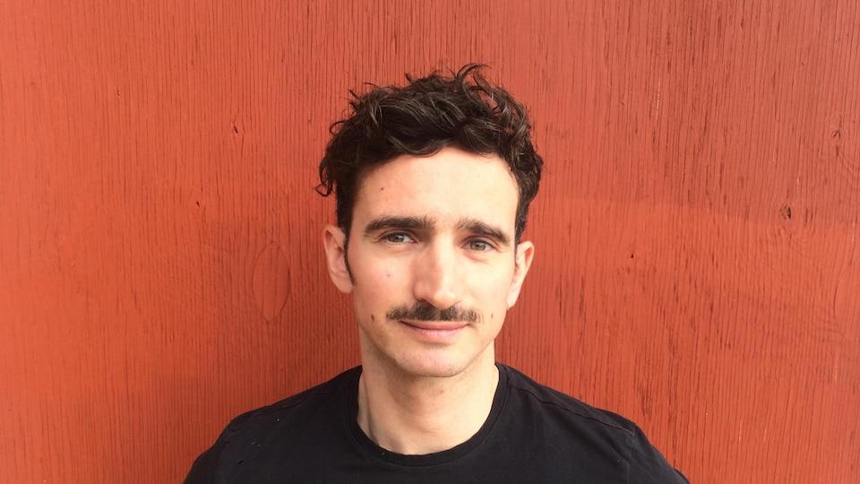 Un jeune homme aux cheveux châtains courts avec une moustache. Il porte un chandail noir, a les yeux verts et il pose en face d'un mur orange.