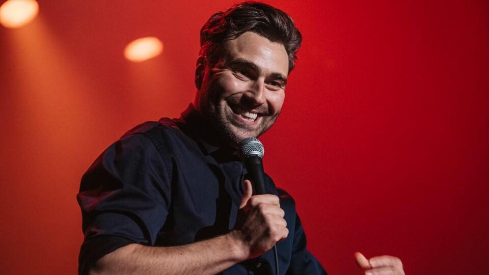 Un homme, souriant, tient un micro de scène d'une main et gesticule d'une autre. Il sourit en regardant son public.