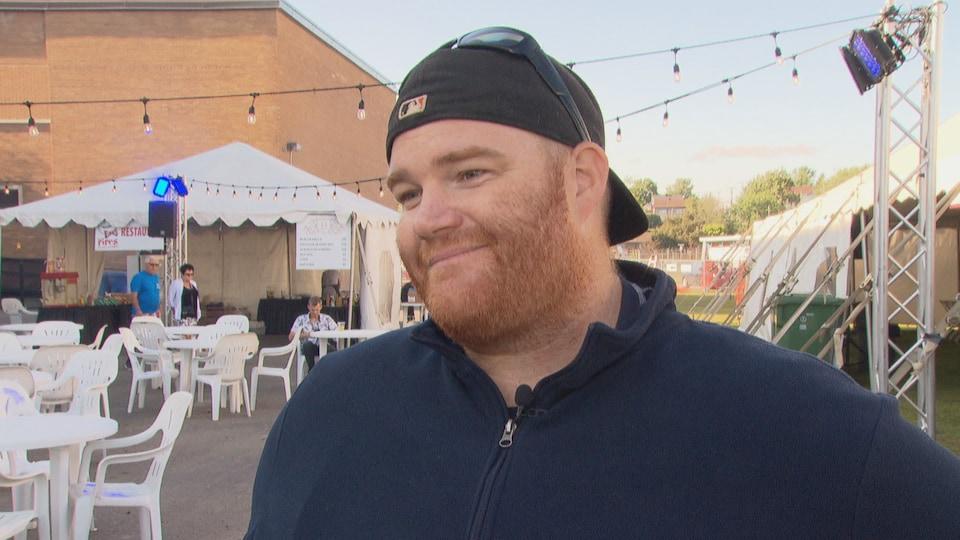 Un homme portant une casquette et un chandail foncés sourit, placé devant un chapiteau.
