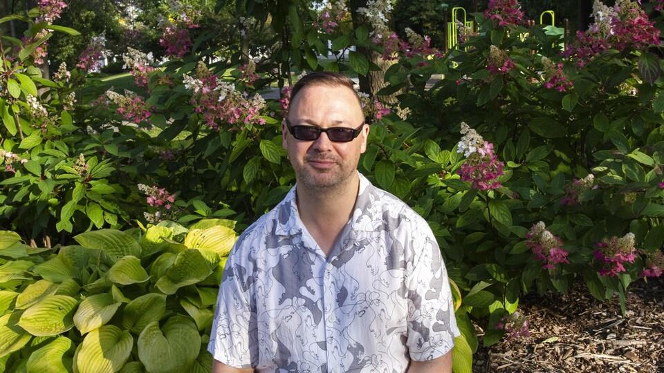 Simon Tardif est assis devant des fleurs.