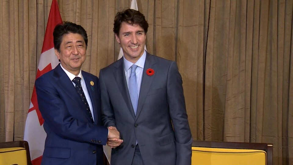 Le premier ministre japonais, Shinzo Abe, serre la main de Justin Trudeau au sommet de l'APEC, au Vietnam.