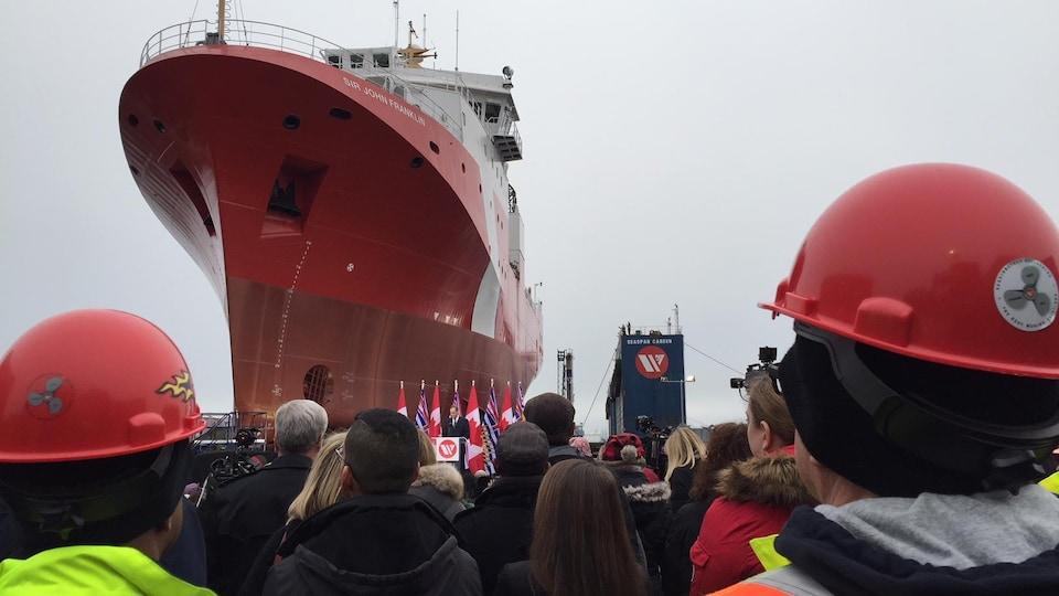 Des travailleurs admirent le grand navire rouge et blanc