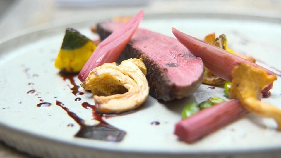 Du canard servi dans une assiette avec des légumes et un sirop d'hibiscus