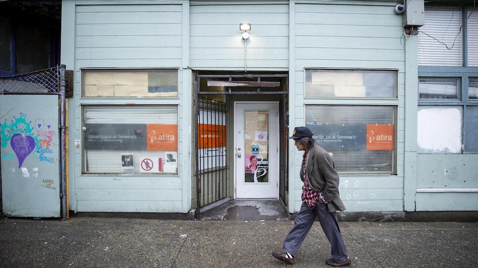 Une personne marche devant le centre d'injection supervisée SisterSpace, dans le quartier du Down Town East Side.