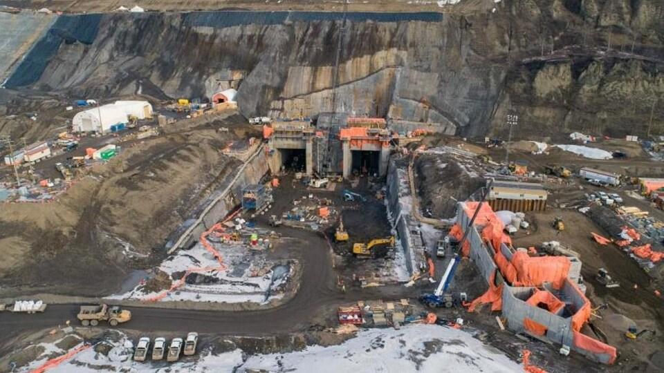 Aperçu d'un chantier de construction et du percement d'un tunnel dans une colline.