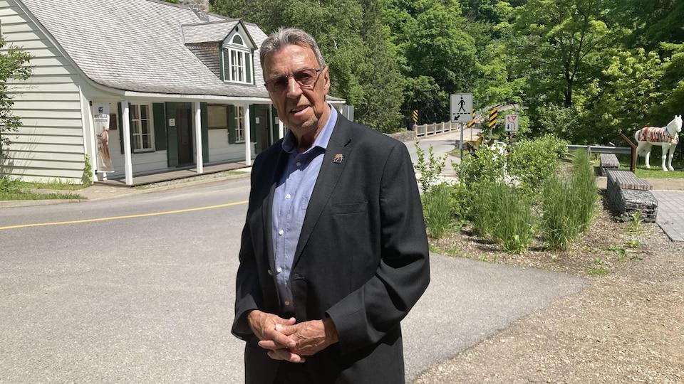 Un homme cheveux blancs, lunettes sur le nez prend la pose dehors devant une maison.