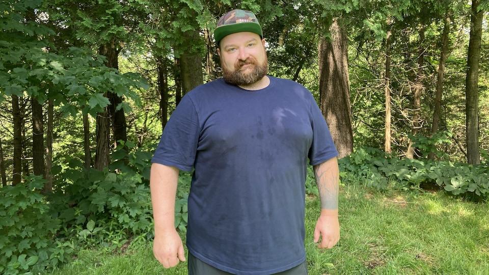 Un homme barbu, casquette sur la tête et tee-shirt à manches courtes, se tient droit et regarde devant lui.
