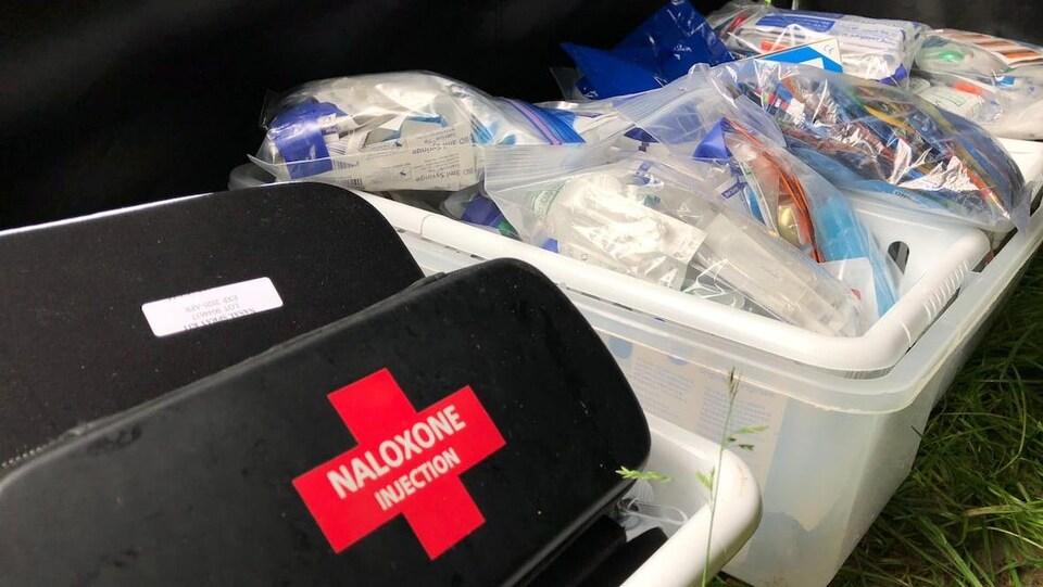 Des bacs en plastique installés à même le sol contiennent des trousses de naloxone et du matériel médical du type auguilles et pansements