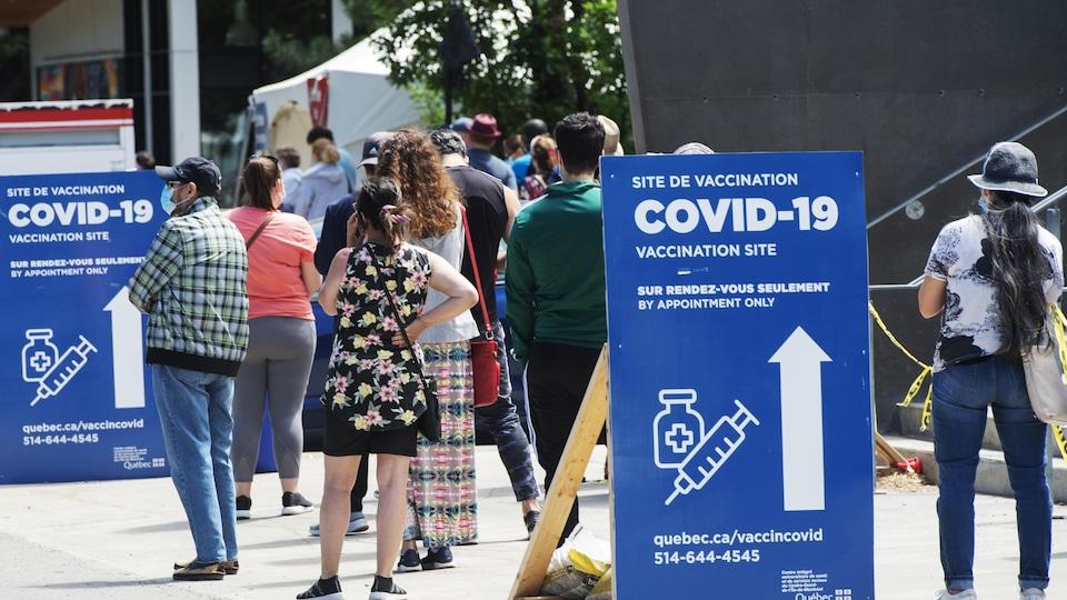 Des gens font la file à l'extérieur d'un site de vaccination contre la COVID-19.