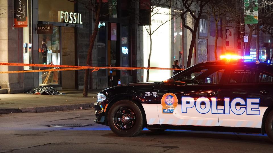 Un véhicule du Service de police de la Ville de Montréal au premier plan et un corps d'un corps recouvert d'une couverture plus loin sur le trottoir.