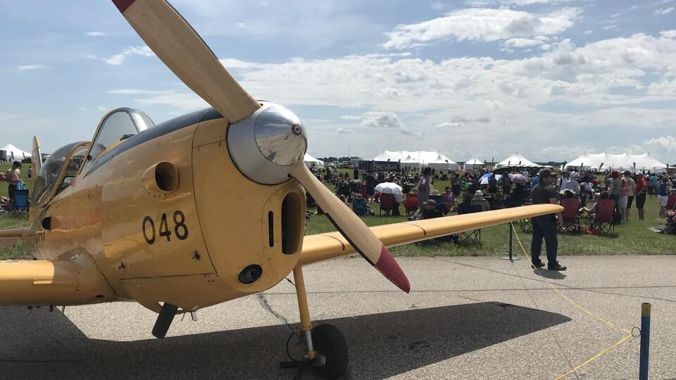Le devant d'un avion à hélice vu de près avec, en arrière-plan, une foule assemblée sur l'herbe.