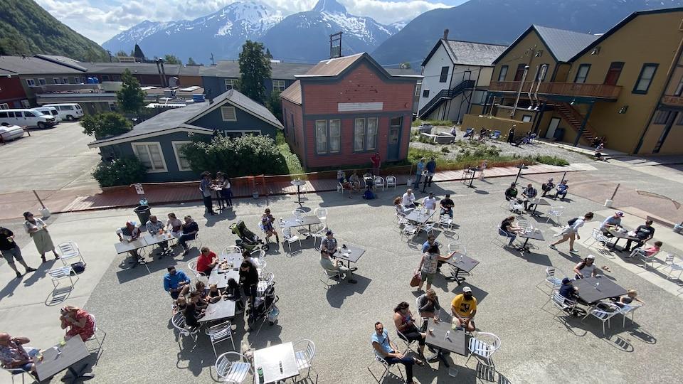 Des tables et des clients sont installés au milieu de la rue avec les montagnes en arrière-plan.