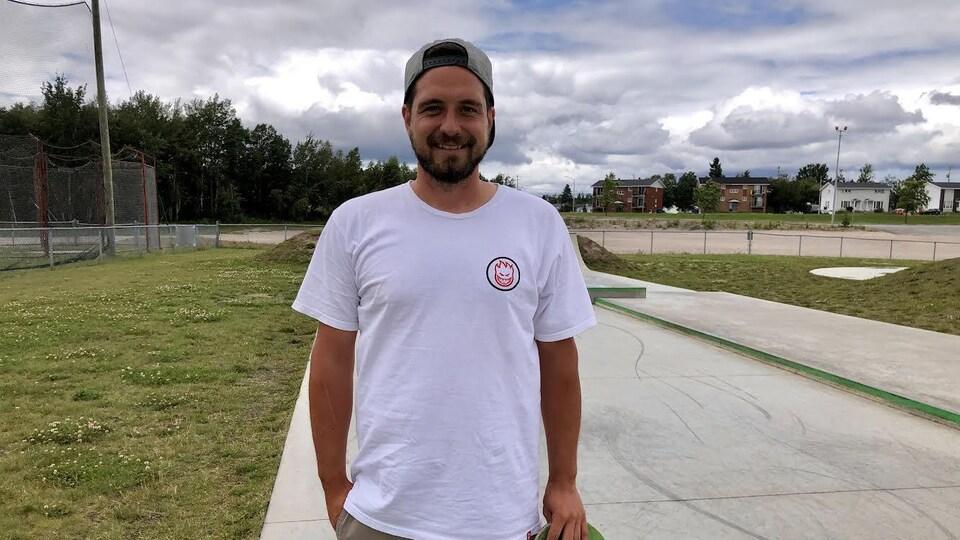 Frédérick Cloutier tient sa planche à roulette devant le skate park.