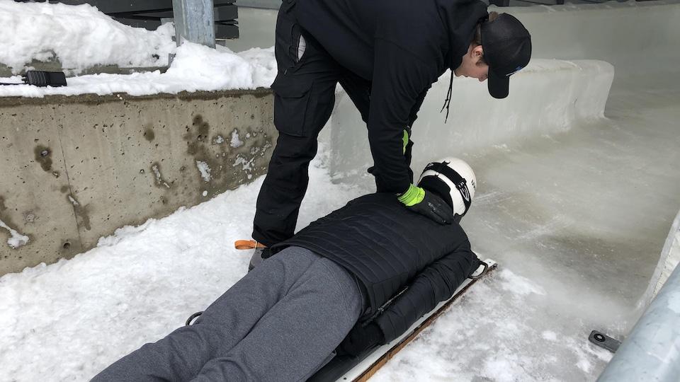 un homme debout pousse un autre homme allongé sur une plache de glisse.
