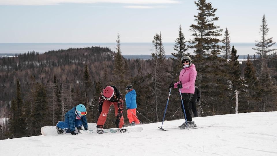Une adulte en ski et deux jeunes en planche à neige en haut d'une pente.