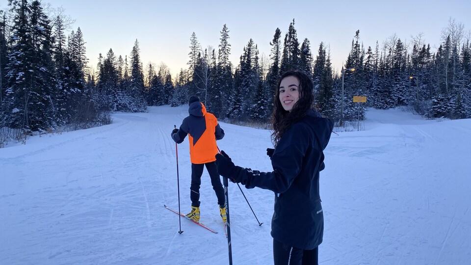 Femme dehors en ski qui sourit.