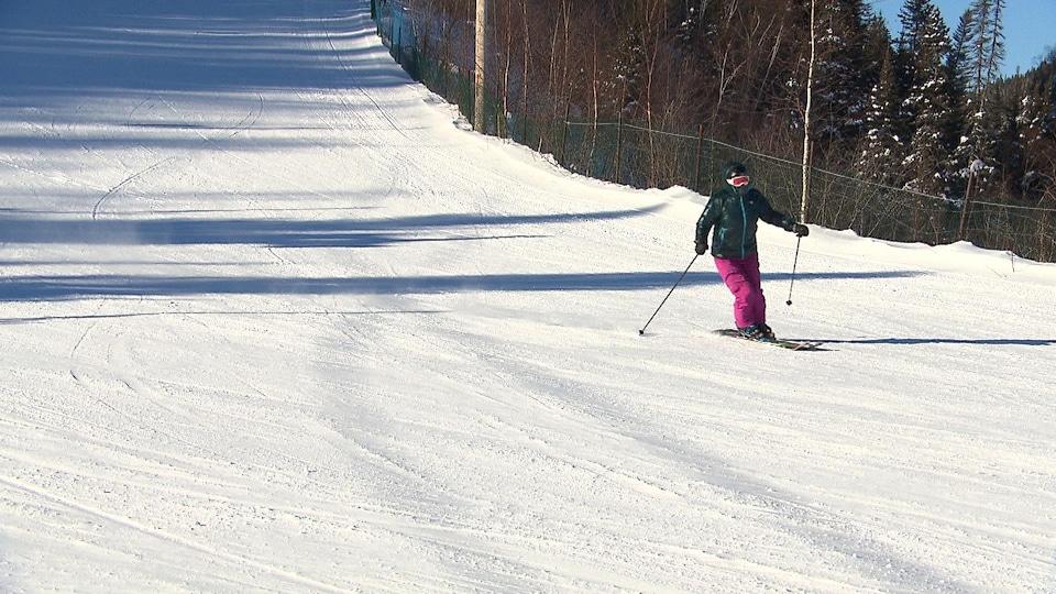 Une femme skie seule sur une piste enneigée, en bordure d'une forêt.