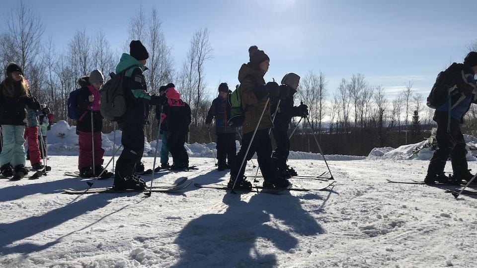 Des élèves en ski raquette se promènent sur un terrain plat enneigé.