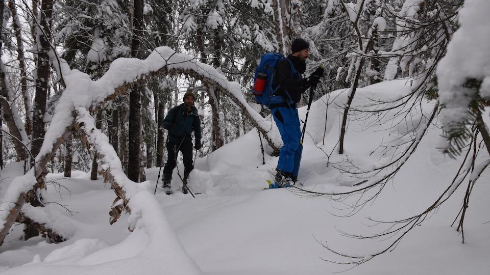 Deux skieurs en train de gravir une montage en raquettes.