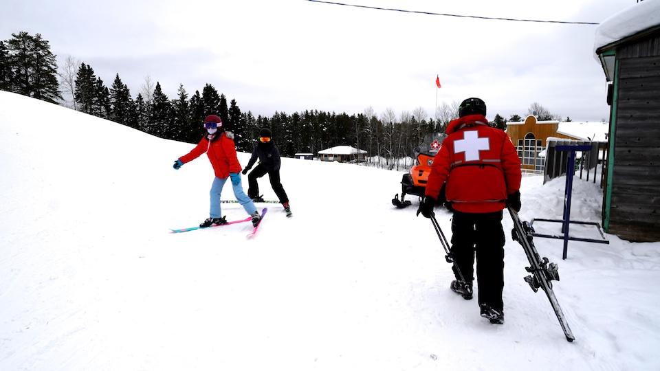 Un homme avec ses skis en main et deux jeunes sont à ses côtés.